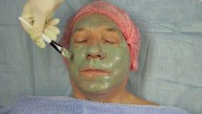 Ein männlicher Cosmetologist, der Handschuhe trägt, setzt eine Schlammmaske auf das Gesicht eines client's Kunden mit einer spe stock video footage