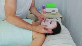 Ein männlicher Cosmetologist wendet eine befeuchtende Gesichtsmaske an einer Klientin in einem Badekurortsalon an stock video