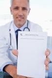Ein männlicher Doktor, der ein unbelegtes Verordnungblatt zeigt Stockbilder
