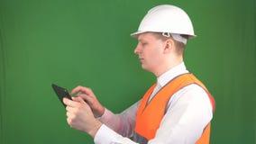 Ein männlicher Ingenieur in einem Schutzhelm und Signalwestenstände mit einer Tablette auf einer Baustelle, macht die Anmerkungen stock footage