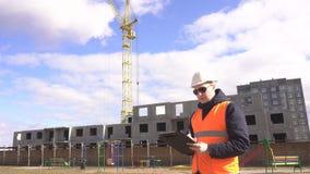 Ein männlicher Ingenieur mit schwarzen Gläsern in einem Sturzhelm und in einer Signalweste notiert und markiert in einer Tablette stock footage