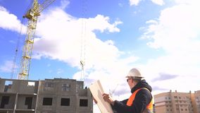 Ein männlicher kaukasischer Ingenieur ist ein Designer in einer Signalweste und in einem Sturzhelm, der in einen Plan nach dem Ba stock video footage