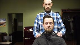 Ein männlicher Kunde, der seinen Schnurrbart und Bart an einem Friseursalon sich pflegen lässt stock video footage