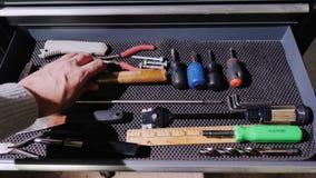 Ein männlicher Meister öffnet ein Fach mit Werkzeugen und nimmt einen Maßband und einen Hammer stock video footage