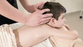 Ein männlicher Physiotherapeutenmasseur macht einem kleinen lächelnden Jungen eine Entspannungsmassage der Heilung, der auf einem stock footage