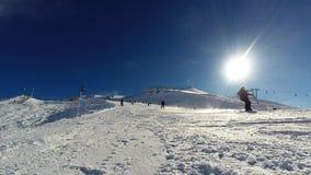Ein männlicher Skifahrer, der abwärts Ski fährt und vor der Kamera stoppt stock footage
