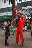 Ein männlicher Stelzenwanderer im roten Clownkostüm, das Hände rüttelt stockfoto