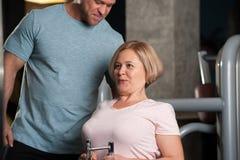 Ein männlicher Trainer hilft seinem weiblichen Kunden stockbild