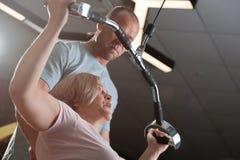 Ein männlicher Trainer zeigt, wie man die Übungen tut lizenzfreie stockfotos