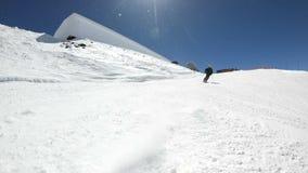Ein männlicher WeitwinkelSkifahrer gealtert in der schwarzen Ausrüstung und im weißen Sturzhelm mit Skipfostenfahrten auf eine sc stock footage