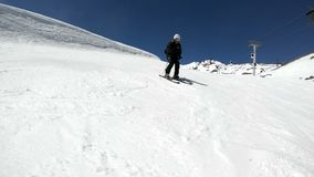 Ein männlicher WeitwinkelSkifahrer gealtert in der schwarzen Ausrüstung und im weißen Sturzhelm mit Skipfostenfahrten auf eine sc stock video