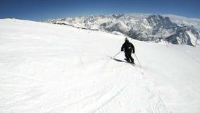 Ein männlicher WeitwinkelSkifahrer gealtert in der schwarzen Ausrüstung und im weißen Sturzhelm mit Skipfostenfahrten auf eine sc stock video footage