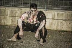 Ein männlicher Zombie, der an in der leeren Stadtstraße sitzt Stockfoto