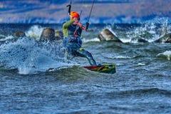Ein männliches kiter schiebt auf die Oberfläche des Wassers Spritzt von der Wasserfliege auseinander lizenzfreie stockfotografie