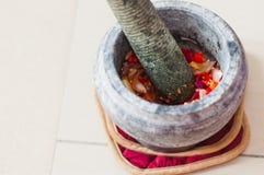 Ein Mörser und Stampfe oder lesung batu auf Malayisch mit zerquetschten Paprikas, gebratenen Schalotten und Garnelenpaste mischte Lizenzfreies Stockbild