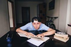 Ein müder Student liegt um einen Schreibtisch nahe Büchern und Notizbüchern bei der Ausführung der Aufgabe Zu Hause unterrichten  stockfoto