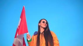 Ein M?dchen in einer gelben Jacke und Glasgriffe in ihrer Hand die Flagge von Kanada Die Flagge von Kanada entwickelt sich im Win stock video