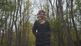 Ein M?dchen in einer warmen schwarzen Jacke geht durch das Holz Das M?dchen folgt der Kamera schie?t von oben bis unten stock video footage