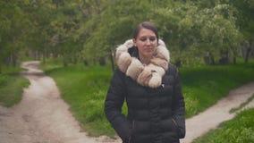 Ein M?dchen in einer warmen schwarzen Jacke geht durch das Holz Das M?dchen folgt der Kamera stock video footage