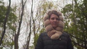 Ein M?dchen in einer warmen schwarzen Jacke geht durch das Holz Das Mädchen folgt der Kamera schießt von oben bis unten stock footage