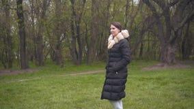 Ein M?dchen in einer warmen schwarzen Jacke geht durch das Holz Das M?dchen und die Kamera ziehen parallel um stock video