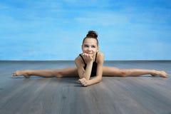 Ein M?dchenturner in einem schwarzen gymnastischen Badeanzug sitzt auf Querspalten auf dem Hintergrund des blauen Himmels stockfotos
