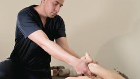 Ein m?nnlicher Physiotherapeut tut eine Energie, die f?r einen m?nnlichen Patienten zu einem jungen b?rtigen Hippie in einem Raum stock footage