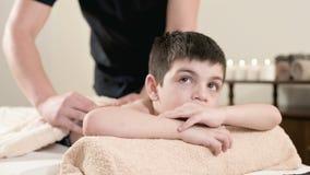 Ein m?nnlicher Physiotherapeutenmasseur macht einem kleinen Jungen eine Entspannungsmassage der Heilung, der auf einem Massagebet stock video footage