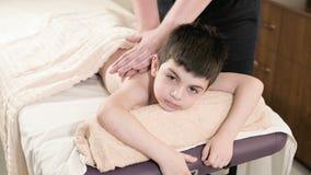 Ein m?nnlicher Physiotherapeutenmasseur macht einem kleinen Jungen eine Entspannungsmassage der Heilung, der auf einem Massagebet stock footage