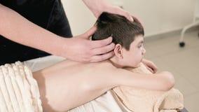 Ein m?nnlicher Physiotherapeutenmasseur macht einem kleinen l?chelnden Jungen eine Entspannungsmassage der Heilung, der auf einem stock video footage