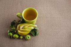 ein Mag mit Apfelsaft, einer Niederlassung mit grünen unausgereiften Äpfeln und einem gelockten Ausschnittapfel Lizenzfreie Stockfotos