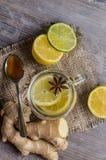 Ein maison Glas mit Ingwer- und Zitronentee mit Pillen und Thermometer auf dem hölzernen Hintergrund Stockbild