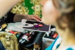 Ein Make-upwerkzeug in den Händen einer Frau, die Make-up tut stockfoto