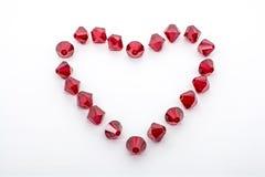 Ein Makroschuß einer Sammlung roter Perlen in Form eines Herzens Stockfotografie