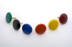 Ein Makroschuß einer Sammlung von sechs farbigen Reißzwecken Stockfotos