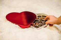 Ein man& x27; s-Hand, die für einen Kasten Schokoladen erreicht Stockbild