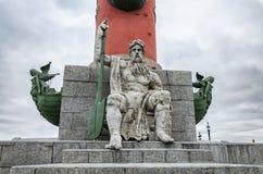 Ein man& x27; s-Zahl mit zwei Podien, die am Fuß der Podiumsspalte auf dem Spucken von Vasilievsky-Insel sitzen Lizenzfreies Stockfoto