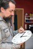 Ein Mann ändert die Zeit auf einer Uhr stockbilder