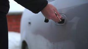 Ein Mann öffnet den Schlüssel zur gefrorenen Autotür Es ist sehr kalt stock video footage