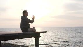 Ein Mann übt Yoga durch den Ozean stock video