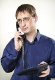 Ein Mann am Arbeit whith Telefon Lizenzfreies Stockfoto