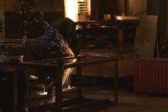 Ein Mann in Arbeitsformschnitten, die ein Metall mit einem Bulgaren sah stockbilder