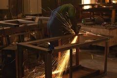 Ein Mann in Arbeitsformschnitten, die ein Metall mit einem Bulgaren sah lizenzfreie stockfotografie
