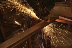 Ein Mann in Arbeitsformschnitten, die ein Metall mit einem Bulgaren sah lizenzfreies stockfoto