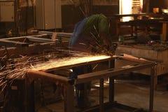 Ein Mann in Arbeitsformschnitten, die ein Metall mit einem Bulgaren sah stockfoto