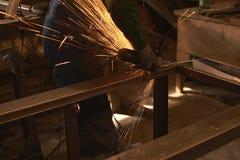 Ein Mann in Arbeitsformschnitten, die ein Metall mit einem Bulgaren sah lizenzfreies stockbild