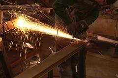 Ein Mann in Arbeitsformschnitten, die ein Metall mit einem Bulgaren sah lizenzfreie stockfotos