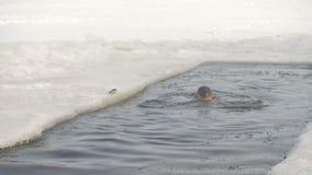 Ein Mann atmet tief ein, um unter gefrorenem Wasser zu erhalten stock video