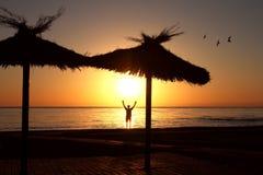 Ein Mann auf dem Strand begrüßt den Sonnenaufgang mit seinen Händen oben stockfotos