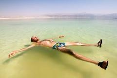 Ein Mann auf dem Wasser des Toten Meers in Israel Lizenzfreie Stockfotos